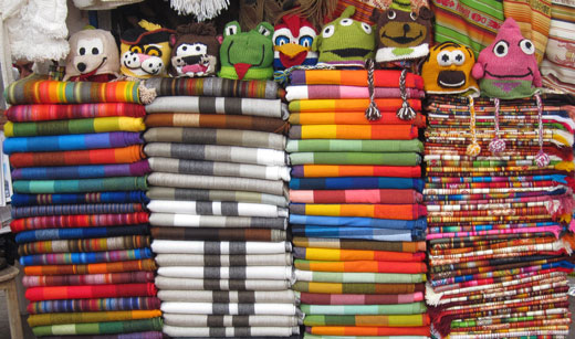 Stacks of colorful blankets at the craft market in Otavalo.