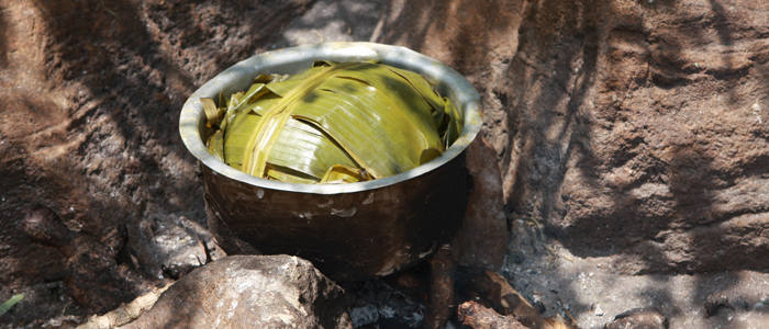 A banana leaf wrapped dish cooked on a wood fire.